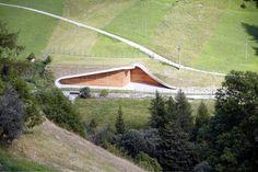 Una central hidroeléctrica que respeta el paisaje  Uno de los mayores inconvenientes de las centrales hidroeléctricas es su impacto visual en el paisaje.  Esto es especialmente relevante cuando se encuentran en zonas naturales. Existen estructuras sin ningún tipo de integración en el entorno incluso en parques nacionales.   Ésta central proyectada por el estudio de arquitectura Monovolume Architecture y construida en el Tirol italiano contrasta