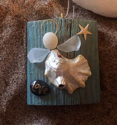 Driftwood ornament 2.5 x 3 inches. Graceful little angel made of oyster shell which has a natural barnacle which adds some character. Her head is a Cape May pebble and wings are genuine seaglass found on local beach and she has a swarovski chrystal heart. There is a real starfish #homemadeseaglass