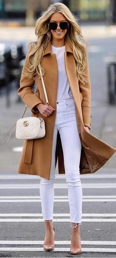 #spring #outfits selective focus photography of woman in brown long coat standing on pedestrian. Pic by @manhattan_fashion_styles #fashionoutfits