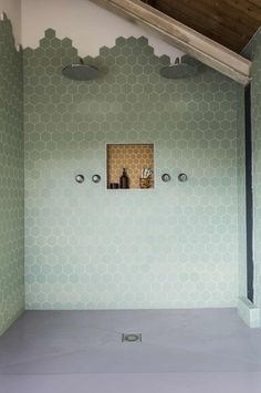 Love that muted sage green shower wall of Honeycomb tile!! The organic top is one of the best parts :)