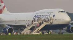 BA plane with passengers being led off