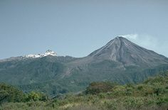A steam plume blows from the summit of Mexico's Colima volcano in this 1992 view from the WSW with snow-capped Nevado de Colima to the left. Colima, also known as Fuego de Colima, is one of North America's most active volcanoes. Frequent eruptions have been recorded since the 16th century. A complex succession of eruptions that has been dominated during the past century by lava effusion associated with lava dome growth has also produced explosive eruptions of varying magnitude and frequent…