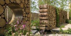 Wood log wall in garden with eyelets. Hugo Bugg landscape design