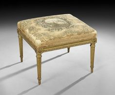 "Louis XVI Giltwood Stool, late 18th century, the padded rectangular top retaining the original fabric, with scrolling foliate patterns centering an oval avian medallion, above a molded frame, raised on fluted tapering circular legs headed by foliate medallions and ending in toupie feet, h. 17"", w. 22"", d. 20"". Provenance: mac MAISON, ltd., New Orleans, Louisiana. New Orleans Auction Galleries, 07.2015 / Lot 60."