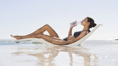 BLOG: THE AMAZING BENEFITS OF DRINKING WATER https://janesuniverse.wordpress.com/2015/04/29/drink-fresh-water-benefits/  PHOTO: Young woman in a bikini drinking a bottle of cold water while enjoying the sunshine.