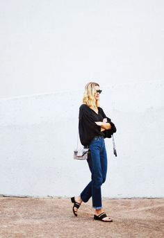 Black flowing top with tassels, denim jeans, black sandals, and animal print bag.