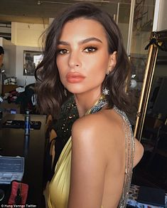 Bronzed beauty: For makeup, the gone Girl actress opted for a golden smokey eye and peachy-nude lipstick over her pouty lips