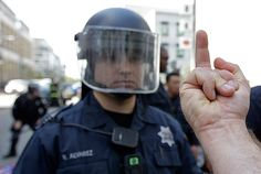 A protestor gestures to an Oakland police officer during May Day protests on May 1, 2012 in Oakland, California.