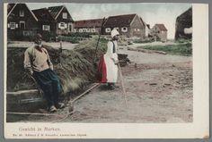 Een oude man en een meisje in Marker dracht met hooinet bij de haven. Een hooinet bestaat uit twee houten stokken met een net ertussen waarin het hooi kon worden vervoerd. 1900-1910 #NoordHolland #Marken