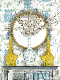 Elizabeth Pyne New York Apartment.  Photo by - NGOC MINH NGO  A vase from Bungalow 5 and a pair of elephant tulipieres pick up the colors of the entry's Follies wallpaper by Tyler Hall. Clarendon mirror, Crate & Barrel.