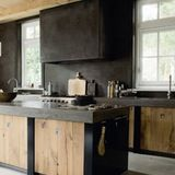 Who says a kitchen has to be cold and clinical? With elements of rough wood, stone, concrete, and brick, these kitchens exude an irresistible rustic warmth.