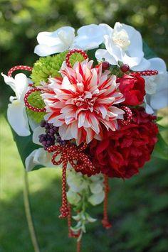 前撮りから使えて、挙式後もお部屋のインテリアとして楽しめる上質なアーティフィシャルフラワー(造花)のウェディングブーケです。【サイズ】直径(約20㎝)×長さ(約25㎝)日本の伝統美、和婚が注目を集めています。色打ち掛けや引き振袖にぴったりの、和のブーケをお作りしました。繊細な紅白の花びらがパッと目を引くダリアや、艶やかな深紅の牡丹、白の胡蝶蘭、つややかな赤い実のヒペリカム、鮮やかなグリーンのマムをあしらい、優しいグリーンの藤の花を垂らしました。赤×金の組み紐を贅沢にお使いし、丁寧に巻き上げました持ち手もよりいっそう和の華やかさをプラスしています。高級感のあります上品なブーケが、花嫁様の和装姿をお美しく輝かせましたら幸いでございます♡★持ち運びに便利な紙製のブーケ専用BOXにお入れしてお届けいたします。 美しさが長持ちして、お部屋の空気をきれいにする光触媒(ひかりしょくばい)加工しています。【光触媒とは】酸化チタンの働きにより、有害物質やホルムアルデヒドなどの有機物を分解、除去します。