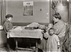 boy and widow rolling papers for cigarettes in NY tenement--1909