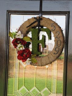 Burlap around a styrofoam wreath, house numbers from Lowe's, and dried moss around a letter initial from a craft store!