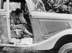 Bonnie and Clyde's bullet-riddled car. Bonnie is slumped in her seat.