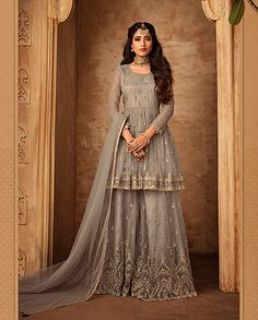 Grey net embroidered sharara suit. This sharara suit is beautified with embroidery all over. It comes with a designer sharara and net dupatta. This sharara suit can be stitched upto bust size 42 inches.