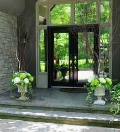 White urns overflowing with hydrangea, hostas, ivy and birch branches welcome guests at the front entrance