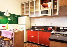 A cozinha projetada pela arquiteta Thais Lenzi Bressiani utiliza o vermelho no armário e em diversos acessórios . Na parede, uma tinta que imita lousa é utilizada para anotar recados e receitas. Para não pesar no ambiente, os armários ganharam portas translúcidas.