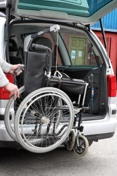 Two-way hoist lifting a folded manual wheelchair into a car boot