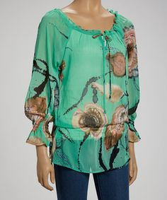 Vibrant color and an eye-catching print make this breezy top pop. With its pretty peasant silhouette and sweet string-tied neck, this fashion-forward piece is sure to put a swing in any style maven's step.