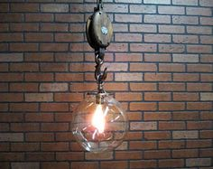 This antique barn pulley hanging light is perfect for your vintage industrial decor. It features a large 10 round clear USA Made Hand Blown glass shade hanging from a wooden and iron pulley. The pulley has been sanded, brushed and stained to renew its great character. This vintage industrial light is 45 long including the canopy. The large cast iron hook is hooked through the sturdy old iron chain, with 2 links, that hangs from the antique brass canopy. It looks fabulous with its…