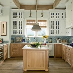 White paint and glass doors on the upper cabinets brighten the kitchen in our…