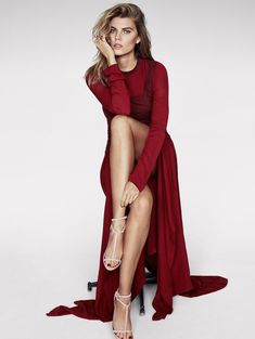 Maryna Linchuk poses in red maxi dress with draped fabric