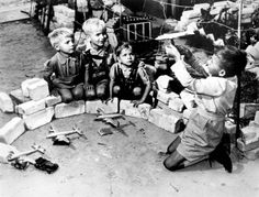 """Berlin Airlift - youngsters who live near the Tempelhof Air Force Base, where the U.S. Air Force transport planes unload their airlift supplies, play at a game called """"Luftbrucke"""" , 1948"""