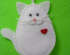 This charming kitty cat measures approx. 4 high x 3 1/2 wide. It is hand cut and sewn and lightly padded with fiberfill. The cats listed are my own design and cannot be an exact replica of every kind and color of cat. I have therefore taken an artistic abstract interpretation of some of the more well known type of cats. The heart button represents the kitty cats love for its guardian. Crafted in a non-smoking home.