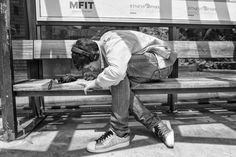 Man on the bench of a bus stop bending over to scratch his lottery card. He is wearing sneakers, headphones and a small umbrella ist lying in front of him.