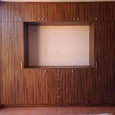 Closet fabricado en Nogal Terracota con espacio para tv.