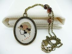 Beige and pale pink silhouette cross stitch necklace