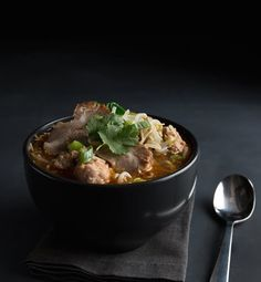 A bowl of hot ramen teeming with spiced meats and garnished with fresh herbs makes for a hearty winter dinner idea