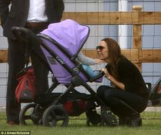 Smiley happy people: Victoria Beckham ditched her signature pout in favour of a big grin as she entertained daughter Harper at the side of a football pitch while son Brooklyn played a match