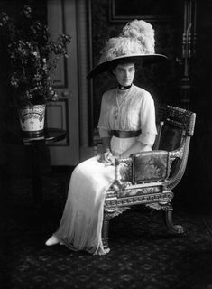 Cecilie seated wearing a wide feathered hat