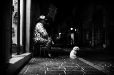 A man and his dog It has been a while since I have been out at night. Mostly because Rethymno is too full of people during the summer and I prefer to shoot lonely figures in the dark. Even so, I took a nocturnal photo walk a couple of weeks ago and I stumbled upon these two. The man was sitting looking at the street, and his little dog was looking around at the people passing by. The little dog was so fluffy and sweet and the old man had no idea I was right next to him. I waited for fluffy…