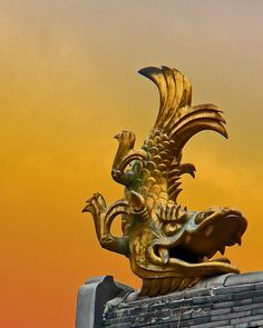 This golden fish with a dragon like-head is called a shachihoko (鯱) were placed on the roofs of gates and castles as they were believed to help prevent fires. According to old Japanese legends, if a fire broke out, they would spit water out of their mouths onto the flames.