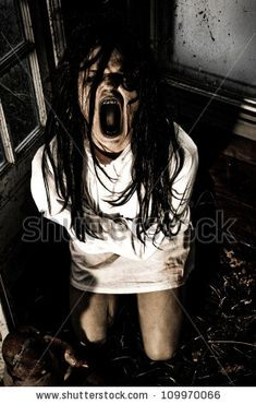 stock photo : Horror Scene of a Woman Possessed Wearing a Straight Jacket Screaming