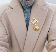 tan coat + blue cable-knit turtleneck seater + gold Chanel brooches