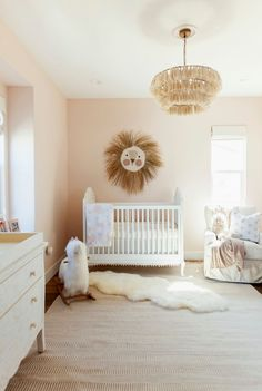 Lovely ivory and pink nursery is illuminated by an ivory tassel chandelier hung over a gold tassel rug layered beneath a white sheepskin rug. Bohemian Nursery, Chic Nursery, Nursery Neutral, Girl Nursery Rugs, Peach Nursery, Gold Nursery Decor, Girl Bedding, Nursery Decals, Nursery Modern