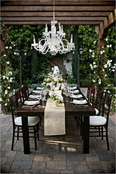 The crystal chandelier is completely unexpected mixed in with the hard textures of the patio and creates drama against the dark stained wool. It ties the tableware in nicely.
