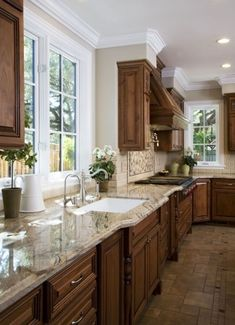 Dark cabinets, light counter tops, medium floor with champaign walls and white windows..♥