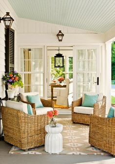 Porch with blue painted ceiling, wicker arm chairs and turquoise outdoor pillows for a pop of bright!