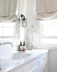 Marble bathroom with soft Roman shades