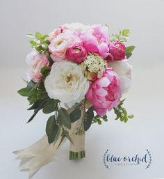 This silk wedding bouquet has pink and cream peonies, ranunculus, garden roses and cabbage roses mixed with greenery.