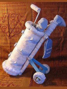 """A couple can never have too many diapers, and what better way to present them than as a cake. There are plenty of """"manly"""" options, from basketball to beer, and you don't need the craft gene to create a masterpiece. This golf set is fairly easy to make once you have the instructions ($9)."""
