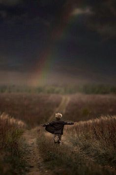 Running toward the rainbow in an angry sky