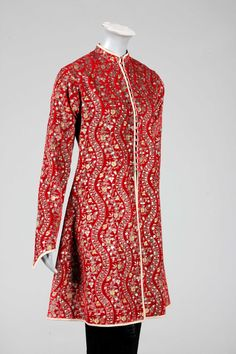 Mariano Fortuny stencilled red velvet jacket, circa 1920-30, the rich deep red velvet stencilled with undulating foliate stripes in gold and silver, the jacket of long slim-fitting oriental shape, with pointed, curved cuffs, piped in grey silk and lined in grey satin, fastened by striped grey glass beads.