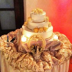 Here is a three tier wedding cake the bottom tier cause gold pearls on the bottom base.each base has gold pearls on the bottom.on the top of each tear has gold flowers made out of buttercream. The cake is made out of smooth white butter cream.