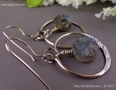 Labradorite - treasured for its remarkable play of color, a shimmering Aurora Borealis. These rough cut gemstones truly shine, with every turn, the color changes right before your eyes...and that flash of blue gets me every single time! I wrought two sterling silver hoops from heavy gauge solid sterling silver - soldered together with a hoop at the top to suspend this mystical stone of protection. These hoops have been given a textured finish at the bottom - to catch the light when one…
